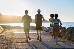 一个小组的后面看法年轻运动朋友跑步 免版税库存照片