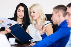 一个小组青年人在一次会议在办公室开会 免版税图库摄影