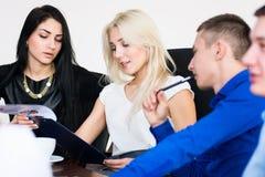 一个小组青年人在一次会议在办公室开会 免版税库存照片