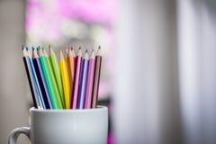 一个小组颜色在一个白色杯子书写 免版税库存图片