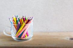 一个小组颜色在木头的一个清楚的杯子书写 免版税图库摄影