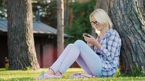 一个少妇使用一个智能手机 坐草在一棵树下在房子的后院 库存图片
