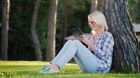 一个少妇使用一种片剂 坐草在一棵树下在房子的后院 库存照片