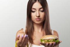 一个少妇做出在健康和有害的食物之间的一个选择 S 免版税库存照片