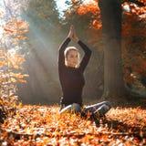 一个少妇做在日出的瑜伽位置 在秋天森林里 免版税库存照片
