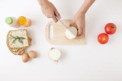 一个少妇准备烹调在白色桌上的每日早餐 库存图片