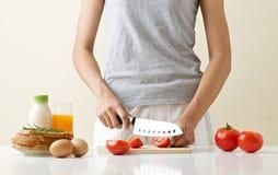 一个少妇准备烹调在白色桌上的每日早餐 图库摄影