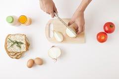一个少妇准备烹调在白色桌上的每日早餐 免版税库存图片