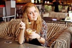 一个少妇吃午餐在咖啡馆笑 免版税库存图片