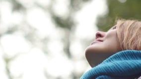 一个少妇呼吸新鲜空气,看与微笑的天空,闭上她的眼睛高兴地 影视素材