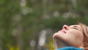 一个少妇呼吸新鲜空气,看与微笑的天空,闭上她的眼睛高兴地 股票录像