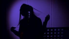一个少妇唱在一个话筒的一首歌曲在录音室在霓虹灯下 免版税图库摄影
