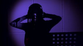 一个少妇唱在一个话筒的一首歌曲在录音室在霓虹灯下 库存图片