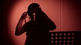 一个少妇唱在一个话筒的一首歌曲在录音室在霓虹灯下 免版税库存图片