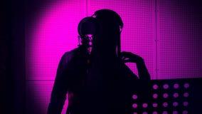 一个少妇唱在一个话筒的一首歌曲在录音室在霓虹灯下 库存照片