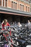 一个少妇在一百辆自行车中间拴住她的自行车,在阿姆斯特丹火车站的停车处 库存图片