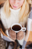 一个少妇在冬天喝一份热的饮料 免版税库存图片