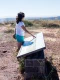 一个少妇在小山站立并且审查戈兰高地的地图 图库摄影