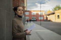 一个少妇在有书的红色墙壁附近站立 免版税库存照片