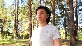 一个少妇在森林周道地看往日落 照相机的运动 影视素材