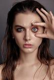一个少妇在演播室张开她的眼睛 免版税库存照片