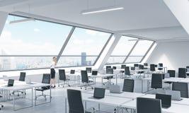 一个少妇在现代明亮的露天场所顶楼办公室看窗口 现代膝上型计算机和b装备的白色桌 图库摄影