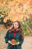 一个少妇在秋天公园走 穿一件绿色外套的深色的妇女 她拿着黄色叶子花束  免版税库存照片
