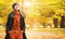一个少妇在秋天在公园给摆在穿衣 免版税库存照片