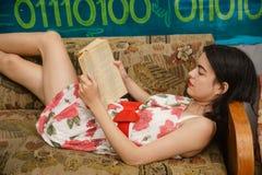 一个少妇在长沙发读一本书 库存照片