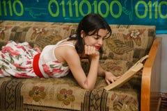 一个少妇在长沙发读一本书 免版税图库摄影
