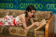 一个少妇在长沙发读一本书 免版税库存照片