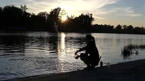 一个少妇坐湖银行投掷的水在日落 股票视频