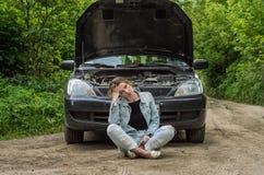 一个少妇打破了在路的一辆汽车,并且她在有一个开放敞篷的一辆汽车前面坐在混乱和等待的帮助与加州 库存照片
