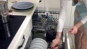 一个少妇放置从洗碗机的一个干净的盘 股票录像