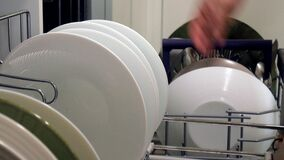 一个少妇放置从洗碗机的一个干净的盘 股票视频