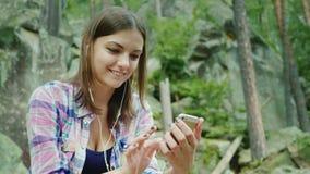 一个少妇游人在远足使用一个智能手机 休息反对在山的岩石的Sits 影视素材