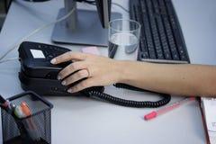 一个少妇特写镜头的手在电话的在办公室 库存图片