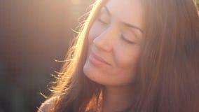 一个少妇特写镜头的美丽的面孔在阳光日落的 股票录像