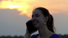 一个少妇由她的智能手机微笑并且叫她的朋友在日落 影视素材