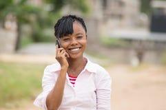 一个少妇的乐趣叫通过显示美好的微笑 免版税库存照片