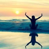 一个少妇的剪影坐海滩在美好的日落期间 免版税图库摄影