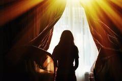 一个少妇的剪影打开帷幕在窗口 库存照片