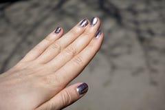 一个少妇的手特写镜头有黑暗的紫罗兰色紫胶修指甲的在钉子 库存照片