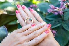 一个少妇的手特写镜头有红色修指甲的在反对自然绿色热带背景的钉子 库存照片