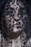 一个少妇的特写镜头看黑的面纱的  免版税库存图片