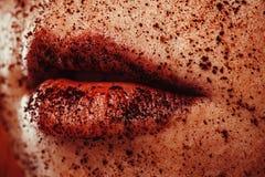 一个少妇的特写镜头画象用在嘴唇和面孔的碾碎的咖啡 库存照片