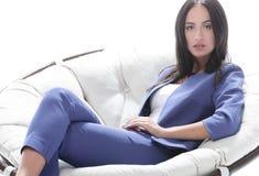 一个少妇的画象一套蓝色衣服的坐一把软的椅子 免版税图库摄影