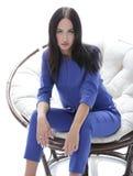 一个少妇的画象一套蓝色衣服的坐一把软的椅子 库存图片