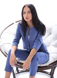 一个少妇的画象一套蓝色衣服的坐一把软的椅子 免版税库存照片
