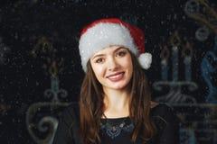 一个少妇的画象圣诞老人盖帽的圣诞节背景的 免版税库存照片